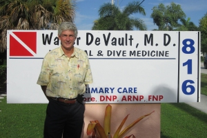 Dr. DeVault in front of sign outside his office